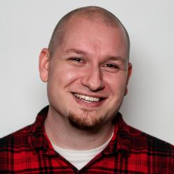 A young, caucasian male smiling with a shaved head and goatee, sporting a red and black plaid shirt.