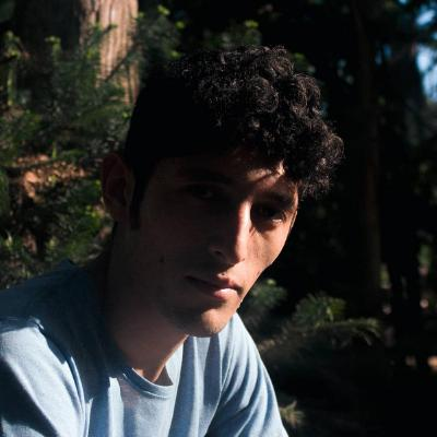 Um rapaz olhando para a câmera com o rosto meio de lado
